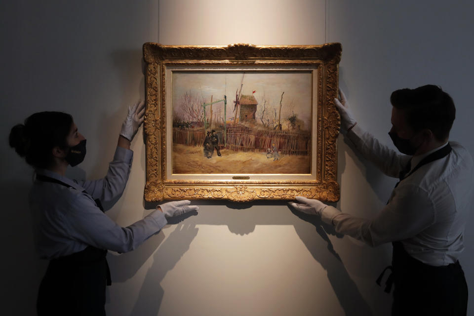 Sotheby's personnel display « Scene de rue à Montmartre » (Street scene in Montmartre), a painting by Dutch master Vincent van Gogh at Sotheby's auction house in Paris, Thursday, Feb. 25, 202. The artwork painted in 1887 is to be on public display for the first time ahead of an auction next month. It has remained in the same family collection for over 100 years, according to the auction house which did not reveal the identity of the owner. (AP Photo/Christophe Ena)