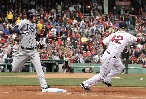Tampa Bay Rays' Matt Joyce beats a wild throw to first for an infield hit as Boston Red Sox first baseman Mike Napoli covers during the second inning of a baseball game at Fenway Park in Boston Monday, April 15, 2013. (AP Photo/Winslow Townson)