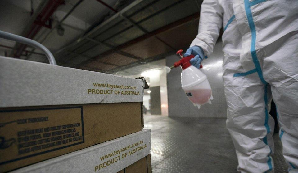 An employee sprays disinfectant on boxes of imported Australian beef at the loading dock of an Ole supermarket in Shanghai on January 19. Photo: Bloomberg