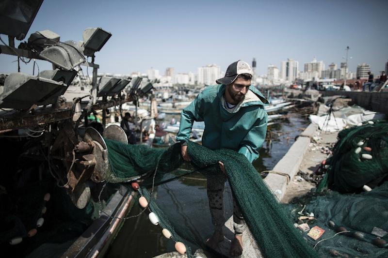 A Palestinian fisherman loads nets onto a boat before sailing into the waters of the Mediterranean Sea in Gaza City on May 3, 2017 after Israel eased restrictions on Gaza fishermen (AFP Photo/Mahmud Hams)