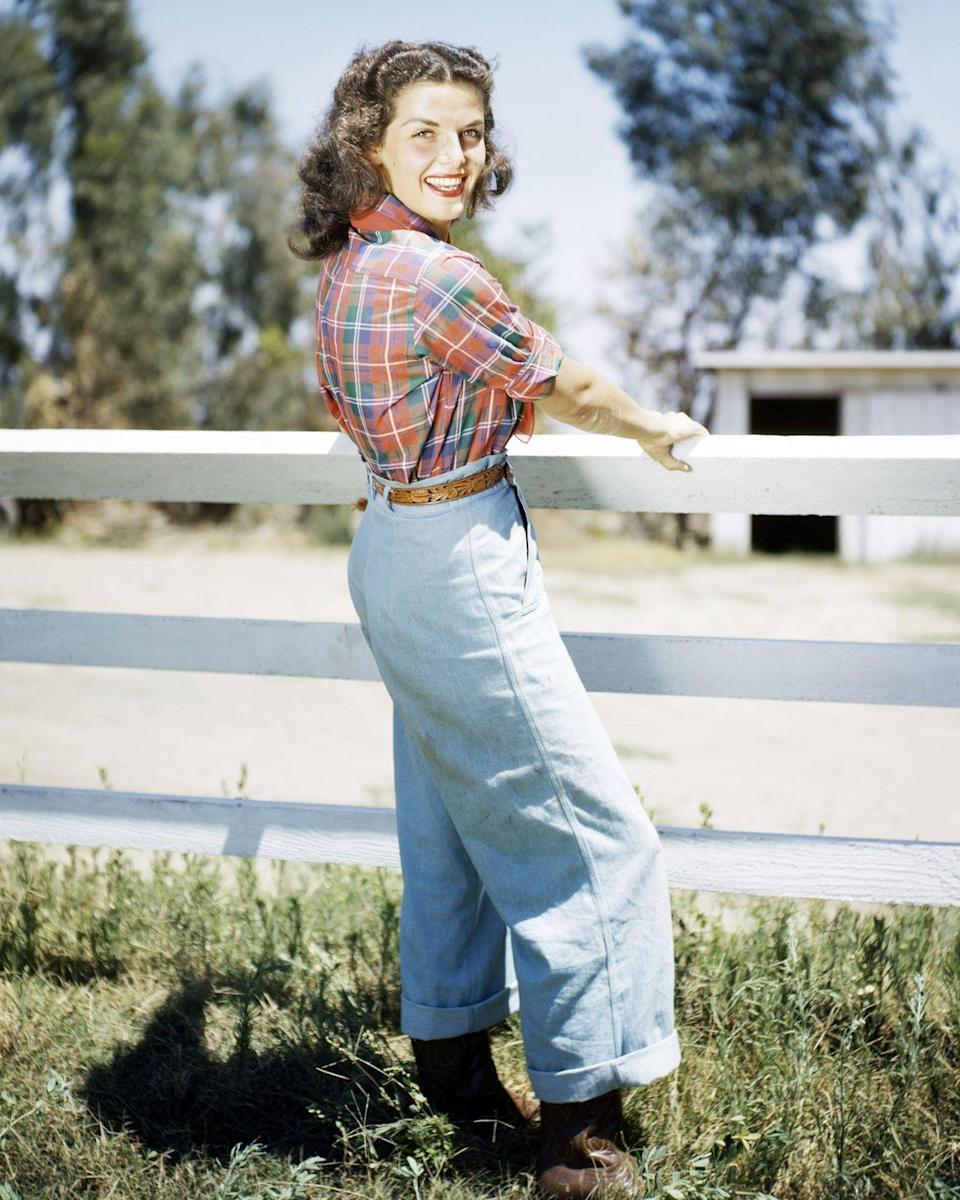 <p>In 1934, Levi's introduced their first pair of women's jeans, which were worn mostly by women who lived on farms and ranches. Sixteen year later, jeans were still linked with that western vibe — but they also had an air of coolness to them. Thanks to Hollywood's popular western films and cowboys being very much in vogue, jeans started appearing in many movies and publicity shots, like this one of actress Jane Russell.</p>
