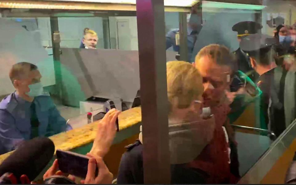Alexei Navalny kisses his wife Yulia as he is detained by police - AP