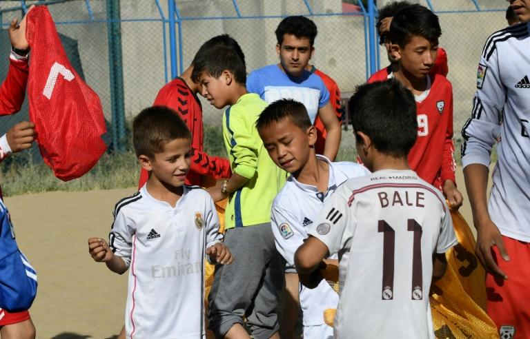 "At a makeshift beach in landlocked Afghanistan, children as young as eight, wearing baggy Real Madrid and Barcelona shirts with ""Ronaldo"" and ""Bale"" printed on the back, joyfully kick and chase the ball"