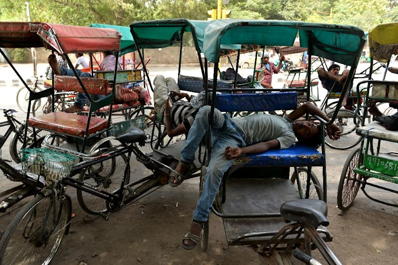 Cycle rickshaw riders sleep during the heatwave in New Delhi on May 28, 2015 (AFP Photo/Chandan Khanna)