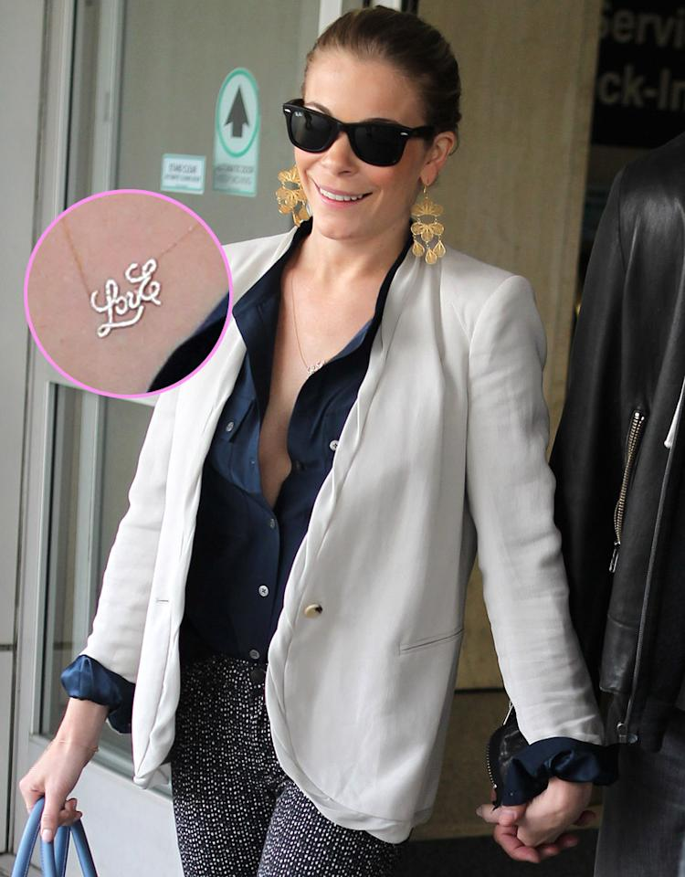 """LeAnn Rimes and husband Eddie Cibrian arrived at LAX after a trip to Indio, Tuscon and Phoenix. LeAnn wore a low-cut blouse with a necklace reading """"LovE,"""" matching a tattoo on her lower back and signifying Love Eddie. Pictured: LeAnn Rimes  Ref: SPL361666  200212  Picture by: MAP  / Splash News   Splash News and Pictures Los Angeles:310-821-2666 New York:212-619-2666 London:870-934-2666 photodesk@splashnews.com"""