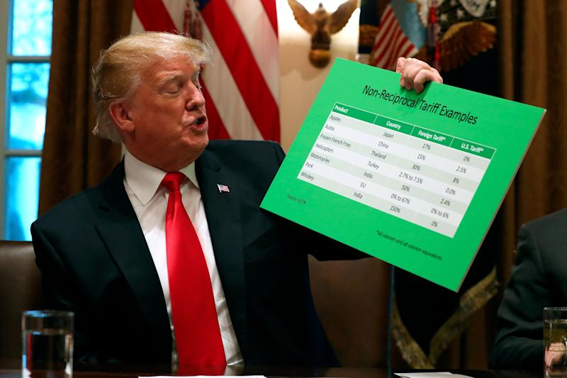 President Donald Trump holds up examples of tariffs, Thursday, Jan. 24, 2019, in the Cabinet Room of the White House in Washington. (AP Photo/Jacquelyn Martin)