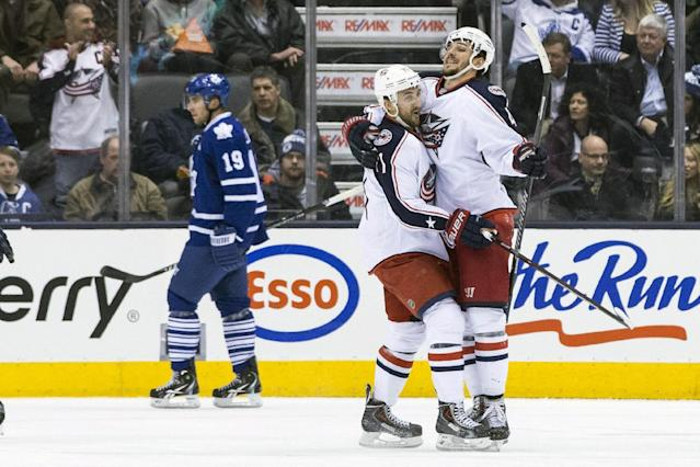 Columbus Blue Jackets Artem Anismov, right, celebrates with Nick Folingo after Anismov scored a goal against the Toronto Maple Leafs during the second period of an NHL hockey game in Toronto on Monday, March 3, 2014. (AP Photo/The Canadian Press, Chris Young)