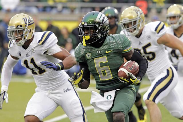 Oregon running back DeAnthony Thomas, middle, turns the corner against UCLA defenders Anthony Barr, left, and Jordan Zumwalt during the first half of an NCAA college football game in Eugene, Ore., Saturday, Oct. 26, 2013. (AP Photo/Don Ryan)
