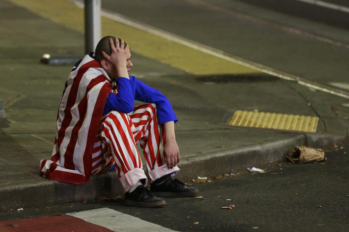 <p>A man dressed in red-white-and-blue sits on the curb during a protest against President-elect Donald Trump, Wednesday, Nov. 9, 2016, in Seattle's Capitol Hill neighborhood. (AP Photo/Ted S. Warren) </p>