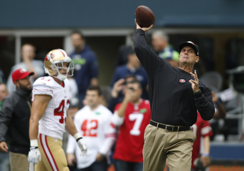 San Francisco 49ers head coach Jim Harbaugh, right, passes during warmups before an NFL football game against the Seattle Seahawks, Sunday, Sept. 15, 2013, in Seattle. (AP Photo/John Froschauer)