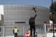 """A protestor holds a cross as he stands on a main entrance door outside Cyprus' national broadcasting buildin, during a protest, in capital Nicosia, Cyprus, Saturday, March 6, 2021. The Orthodox Church of Cyprus is calling for the withdrawal of the country's controversial entry into this year's Eurovision song context titled """"El Diablo"""", charging that the song makes an international mockery of country's moral foundations by advocating """"our surrender to the devil and promoting his worship."""" (AP Photo/Petros Karadjias)"""