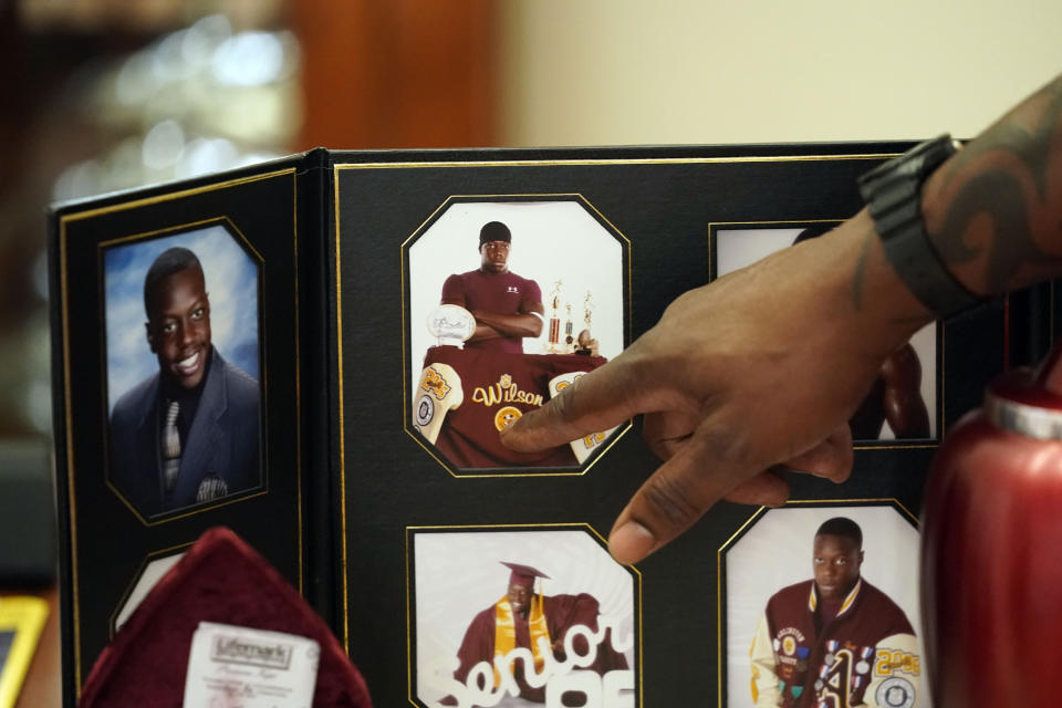 Former U.S. Marine and retired law enforcement officer Marvin Wilson points to a photo of his son Tyrell Wilson on display at his home in Fort Worth, Texas, Monday, May 17, 2021.Tyrell Wilson was shot and killed by Officer Andrew Hall in the San Francisco Bay Area just weeks before prosecutors charged the same officer with manslaughter and assault in the fatal shooting of an unarmed Filipino man more than two years earlier. (AP Photo/LM Otero)