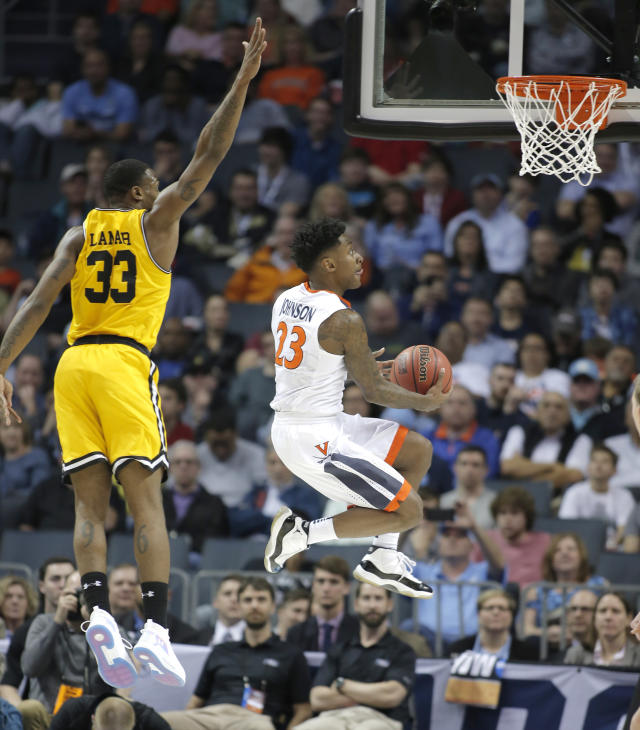 Virginia's Nigel Johnson (23) drives past UMBC's Arkel Lamar (33) during the first half of a first-round game in the NCAA men's college basketball tournament in Charlotte, N.C., Friday, March 16, 2018. (AP Photo/Bob Leverone)