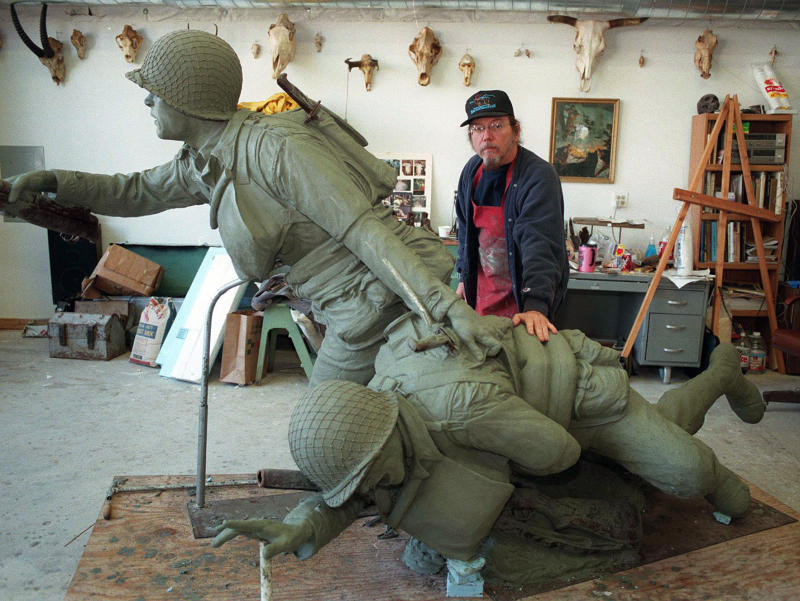 """In this November 1998 photo Kansas sculptor Jim Brothers stands in his Lawrence, Kan., studio with """"Across the Beach,"""" one of several bronze sculptures he has created for National D-Day Memorial in Bedford, Va. Brothers, whose works are part of historical monuments around the country, died Tuesday, Aug. 20, 2013, at his home in Lawrence where he had been in hospice care, according to a funeral director at Warren McElwain Mortuary. He was 72. (AP Photo/Lawrence Journal World, Mike Yoder)"""