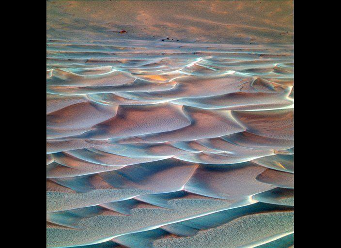 "Sometimes use the rovers' UV and infrared imaging capability to create ""false color"" images of martian terrains, like this view of sand dunes at the bottom of Endurance crater. False color photos are scientifically useful, but they are often just as valuable as garish and lovely artistic renderings that would make Andy Warhol proud... <em> Opportunity rover Pancam image, mission sol 207 (August 23, 2004). From ""Postcards from Mars"" by Jim Bell; Photo credit: NASA/JPL/Cornell University </em>"