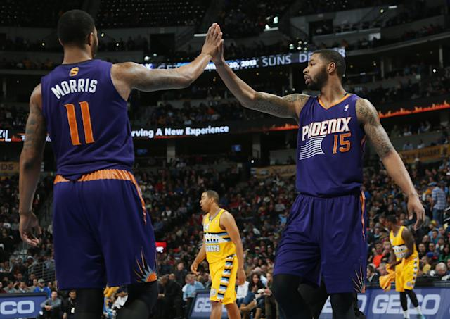 Phoenix Suns forwards Markieff Morris, left, and Marcus Morris congratulated each other after stopping the Denver Nuggets as they drove for a shot in the third quarter of the Suns' 103-99 victory in an NBA basketball game in Denver on Friday, Dec. 20, 2013. (AP Photo/David Zalubowski)