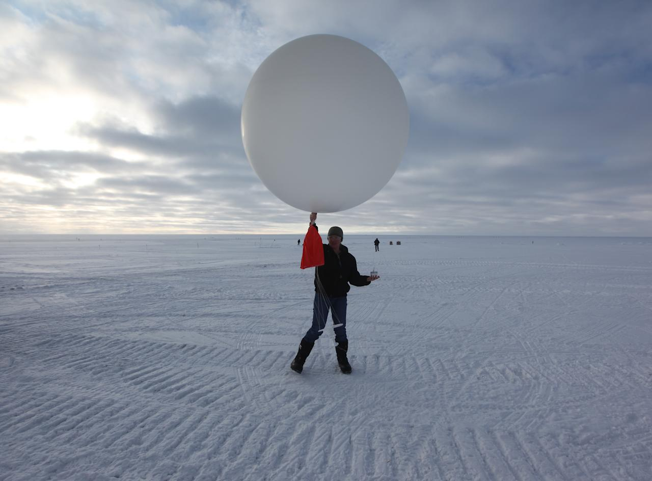 "In this July 15, 2011 photo, atop roughly two miles of ice, technician Marie McLane launches a data-transmitting weather balloon at Summit Station, a remote research site operated by the U.S. National Science Foundation (NSF), and situated 10,500 feet above sea level, on top of the Greenland ice sheet. Climate scientists overwhelmingly agree that manmade greenhouse gases are warming the planet, accelerating the melt of Greenland's ice, and yet resistance to the idea appears to have hardened among many Americans. Why? ""The desire to disbelieve deepens as the scale of the threat grows,"" concludes one scholar who has studied the phenomenon. Analysts now see climate as another battleground in America's left-right ""culture wars."" (AP Photo/Brennan Linsley)"