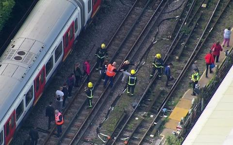 Emergency workers help people to disembark a train near the Parsons Green - Credit: AP