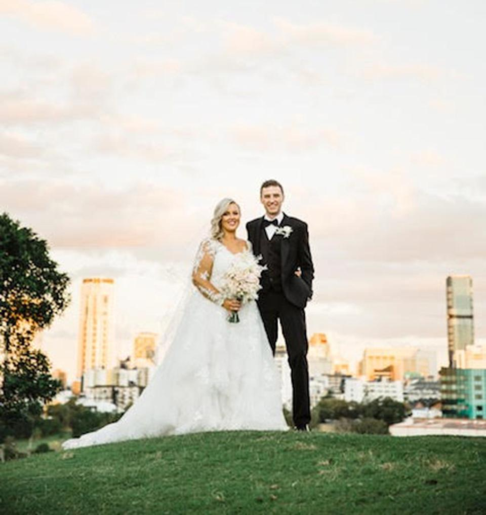 A bride and groom stand together in a park on their wedding day
