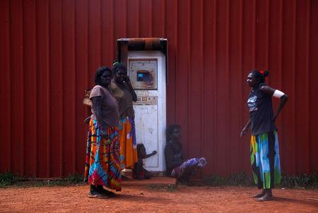FILE PHOTO: Members of the Australian Aboriginal community of Ramingining stand next to a machine used to pay for fuel in East Arnhem Land, located east of the Northern Territory city of Darwin