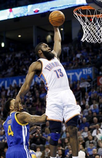 Oklahoma City Thunder guard James Harden (13) dunks in front of Golden State Warriors forward Brandon Rush (4) in the second quarter of an NBA basketball game in Oklahoma City, Friday, Feb. 17, 2012. (AP Photo/Sue Ogrocki)
