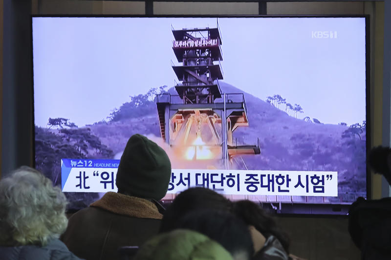 """People watch a TV screen showing a file image of a ground test of North Korea's rocket engine during a news program at the Seoul Railway Station in Seoul, South Korea, Monday, Dec. 9, 2019. North Korea said Sunday it carried out a """"very important test"""" at its long-range rocket launch site that it reportedly rebuilt after having partially dismantled it after entering denuclearization talks with the United States last year. The sign reads: """"Very important test."""" (AP Photo/Ahn Young-joon)"""