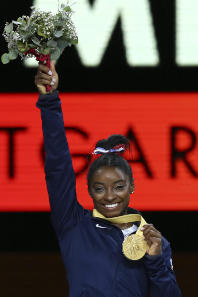 Gold medal winner Simone Biles of the U.S. celebrates on the podium after winning the women's all-around final at the Gymnastics World Championships in Stuttgart, Germany, Thursday, Oct. 10, 2019. (AP Photo/Matthias Schrader)