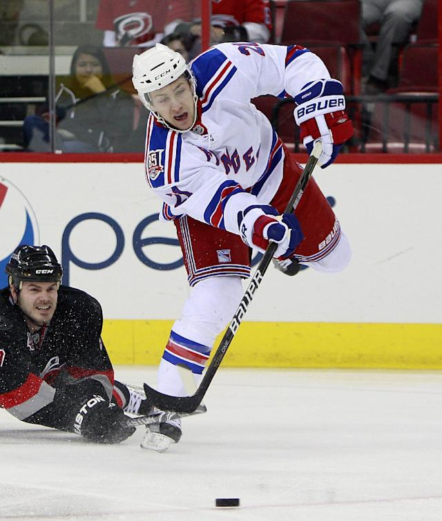 FILE - In this Jan. 20, 2011 file photo, Carolina Hurricanes' Ian White (7) falls to the ice as New York Rangers' Derek Stepan (21) passes the puck during the first period of an NHL hockey game in Raleigh, N.C. Stepan is back in the fold with the Rangers, agreeing to a two-year contract that should have him back on the ice in time for the season opener. A contract was finally worked out Thursday, Sept. 26, 2013, one week before the Rangers start the regular season at Phoenix. (AP Photo/Gerry Broome, File)
