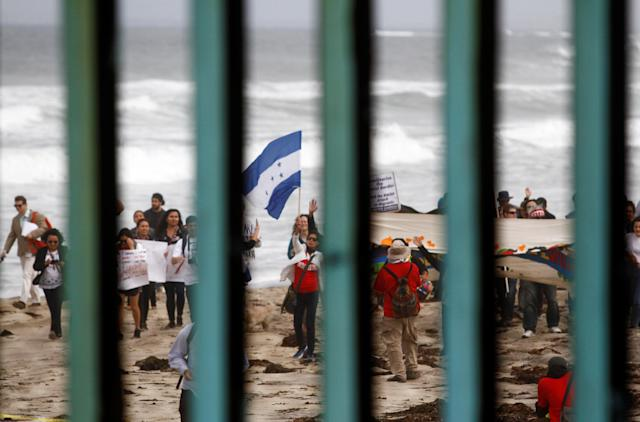 <p>Supporters of a caravan of migrants from Central America wave a Honduran flag while gathering in the United States and near the border fence between Mexico and the U.S. as part of a demonstration prior to preparations for an asylum request in the U.S., as seen through the fence from Tijuana, Mexico April 29, 2018. (Photo: Jorge Duenes/Reuters) </p>
