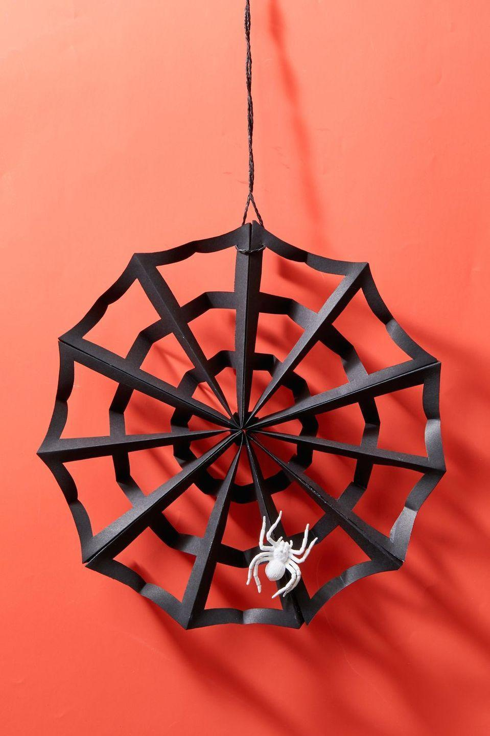 "<p>Like a spooky paper snowflake this wreath is fashioned from black craft paper.<br></p><p><strong>Make the Wreath:</strong> Fold 2 sheets of black paper accordion-style (about 1.5"" inch folds), and then fold each in half lengthwise so you have two segments. Cut the top of the fold diagonally so you'll have a pointed end when it's unfolded. Then, cut three rectangles out of the paper, about half an inch apart, on each part of the segment. Once you have folded and cut both sheets of paper, tie them together tightly at their center folds. Take each loose edge of folded paper and using a glue stick, attach it to the end next to it. You'll see the paper will start to open up like a web! Attach a faux spider with hot glue and hang with black twine.</p><p><a class=""link rapid-noclick-resp"" href=""https://www.amazon.com/SunWorks-Construction-Paper-Black-Sheets/dp/B002LARR7Q/ref=sr_1_12?tag=syn-yahoo-20&ascsubtag=%5Bartid%7C10050.g.22350299%5Bsrc%7Cyahoo-us"" rel=""nofollow noopener"" target=""_blank"" data-ylk=""slk:SHOP BLACK CRAFT PAPER"">SHOP BLACK CRAFT PAPER</a></p>"