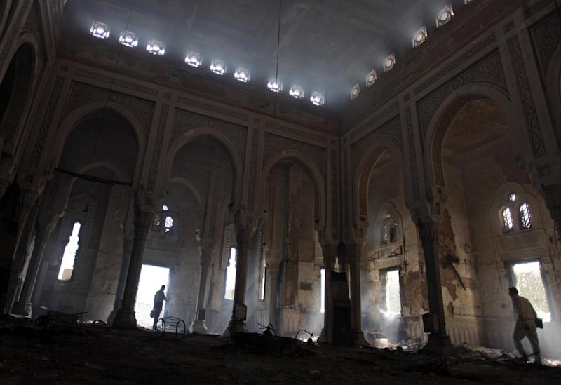 FILE - In this Aug. 15, 2013 file photo, Egyptians tour the inside of the charred Rabaah al-Adawiya mosque, where supporters of Egypt's ousted President Mohammed Morsi had a camp at Nasr City, Cairo. A brutal crackdown on Islamists after a military coup that ousted Egypt's first democratically elected president is posing a dilemma for the country's intellectual elite, which championed greater freedoms during a popular revolt two years ago but now seems largely acquiescent in the wave of arrests and raids targeting the Muslim Brotherhood. (AP Photo/Khalil Hamra)