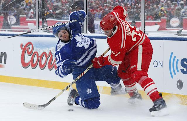 Detroit Red Wings defenseman Kyle Quincey (27) checks Toronto Maple Leafs right wing Phil Kessel (81) during the first period of the Winter Classic outdoor NHL hockey game at Michigan Stadium in Ann Arbor, Mich., Wednesday, Jan. 1, 2014. (AP Photo/Paul Sancya)