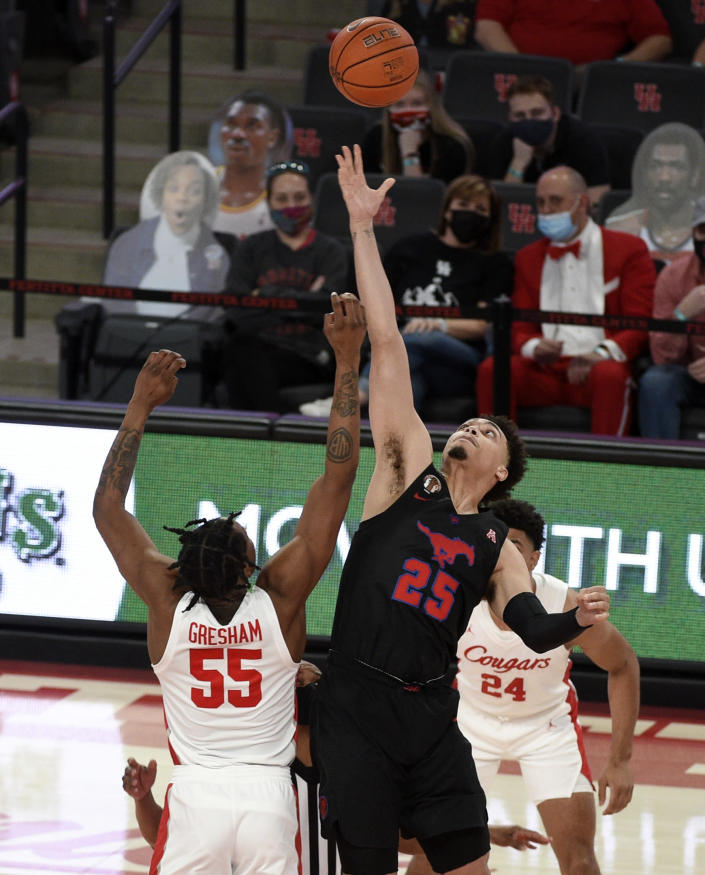 SMU forward Ethan Chargois (25) reaches for the opening tipoff over Houston forward Brison Gresham (55) during the first half of an NCAA college basketball game, Sunday, Jan. 31, 2021, in Houston. (AP Photo/Eric Christian Smith)