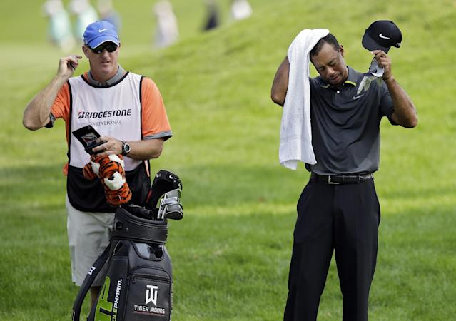 Tiger Woods wipes his head as he waits to hit to the 10th green with caddie Joe Lacava, left, during the second round of the Bridgestone Invitational golf tournament Friday, Aug. 1, 2014, at Firestone Country Club in Akron, Ohio. (AP Photo/Mark Duncan)