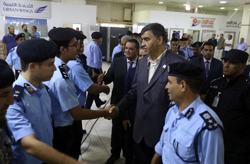 Libyan Interior Minister Abdessalam Ashour (C-R) and undersecretary of the Ministry of Communications in the Al-Wefaq Government Hisham Abu Shkiwat (C-L) greet members of the security forces for Tripoli's Mitiga International Airport