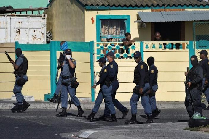 South African police patrol the street during clashes with residents (not visible) of Tafelsig, an impoverished suburb in Mitchells Plain, near Cape Town, on April 14, 2020, after some people in the community did not receive food parcels (AFP Photo/RODGER BOSCH)