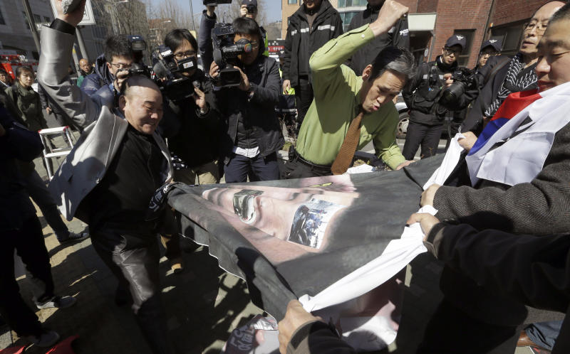 South Korean protesters hit a huge banner with a picture of North Korean leader Kim Jong Un during a rally denouncing North Korea's recent threat and supporting South Korean President Park Geun-hye near the presidential Blue House in Seoul, South Korea, Monday, March 11, 2013. South Korea and the United States began annual military drills Monday despite North Korean threats to respond by voiding the armistice that ended the Korean War and launching a nuclear attack on the U.S. (AP Photo/Lee Jin-man)