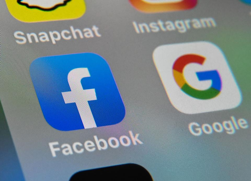 (FILES) This file photo taken on October 1, 2019, shows the logos of mobile apps Facebook and Google displayed on a tablet in Lille, France. - From the Arab Spring to bloodletting in Syria, from Obama to Trump, from terror in the streets of Paris to Brexit, the 2010s began with hope for a more equitable world, and end with a slide towards nationalistic populism. (Photo by DENIS CHARLET / AFP) (Photo by DENIS CHARLET/AFP via Getty Images)