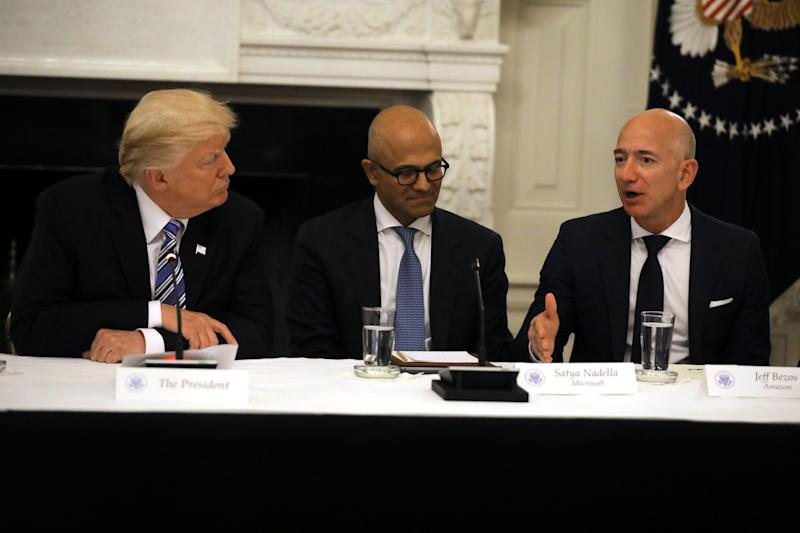 Washington Post owner Jeff Bezos, right, speaks during a meeting with President Donald Trump on June 19, 2017, alongside Microsoft CEO Satya Nadella, center. (Carlos Barria / Reuters)