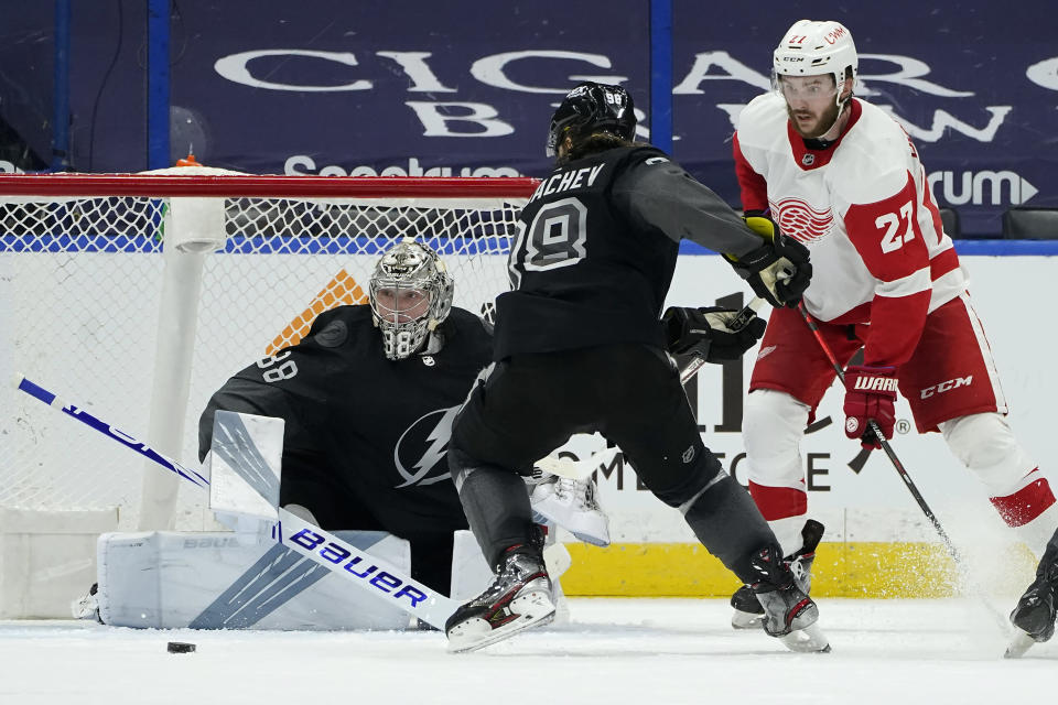 Detroit Red Wings center Michael Rasmussen (27) shoots wide of Tampa Bay Lightning goaltender Andrei Vasilevskiy (88) and defenseman Mikhail Sergachev (98) during the second period of an NHL hockey game Saturday, April 3, 2021, in Tampa, Fla. (AP Photo/Chris O'Meara)