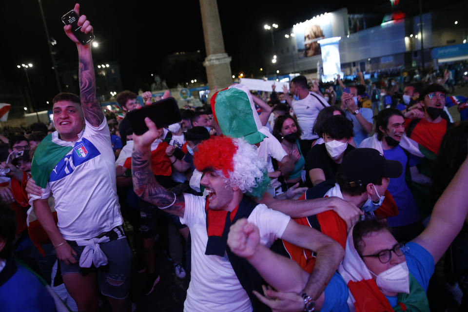 Italian fans celebrate as they watch the Euro 2020, soccer championship group A match between Italy and Turkey, on a mega screen set in downtown Rome, Friday, June 11, 2021. (Cecilia Fabiano/LaPresse via AP)