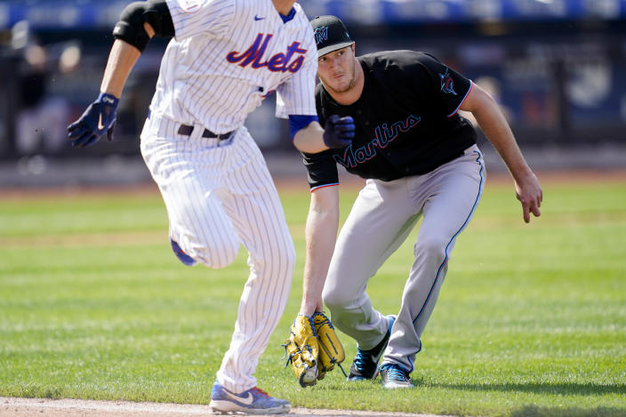 Miami Marlins starting pitcher Trevor Rogers, right, fields and infield single hit by New York Mets' Jacob deGrom, left, in the sixth inning of a baseball game, Saturday, April 10, 2021, in New York. (AP Photo/John Minchillo)