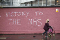 FILE - In this Tuesday, Dec. 8, 2020 file photo, a woman walks past graffiti with the words Victory to the NHS (National Health Service) on a wall at the Royal Victoria Hospital, one of several hospitals around Britain that are handling the initial phase of a COVID-19 immunization program, in West Belfast, Northern Ireland. Britain races to vaccinate more than 15 million people by mid-February, and in an effort to ensure vaccines get to the right places at the right times, along with the syringes, alcohol swabs and protective equipment needed to administer them, the government has called in the army. (AP Photo/Peter Morrison, File)