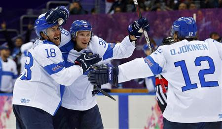 Finland's Juuso Hietanen (C) celebrates his goal against Team USA with teammates Sami Lepisto (L) and Olli Jokinen during the third period of their men's ice hockey bronze medal game at the Sochi 2014 Winter Olympic Games February 22, 2014. REUTERS/Laszlo Balogh