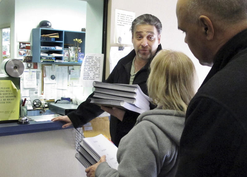 In this Feb. 27, 2014 photo, Eric Stevens, left, delivers a complaint about a court-appointed child guardian in his child custody case to the Connecticut Statewide Grievance Committee in East Hartford, Conn. With him are state Reps. Minnie Gonzalez, center, and Angel Arce, right. Sevens is questioning why his ex-wife, Tiffany Stevens, still has sole custody of their 8-year-old daughter when she is charged with attempted murder on allegations she tried to hire a hit man to kill Stevens. (AP Photo/Dave Collins)
