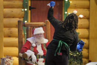 LaToya Booker cleans a transparent barrier between visitors for Santa at a Bass Pro Shop in Bridgeport, Conn., on Nov. 10, 2020. In this socially distant holiday season, Santa Claus is still coming to towns (and shopping malls) across America but with a few 2020 rules in effect. (AP Photo/Seth Wenig)