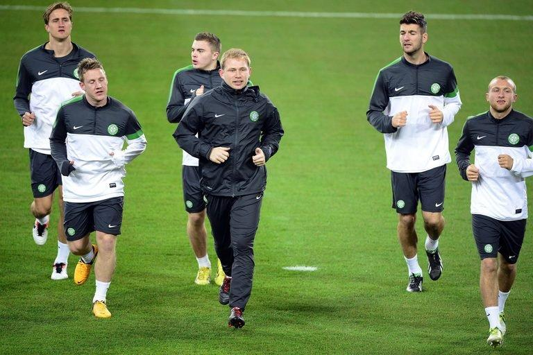 Celtic manager Neil Lennon (C) leads players in a warm up during a training session, March 5, 2013