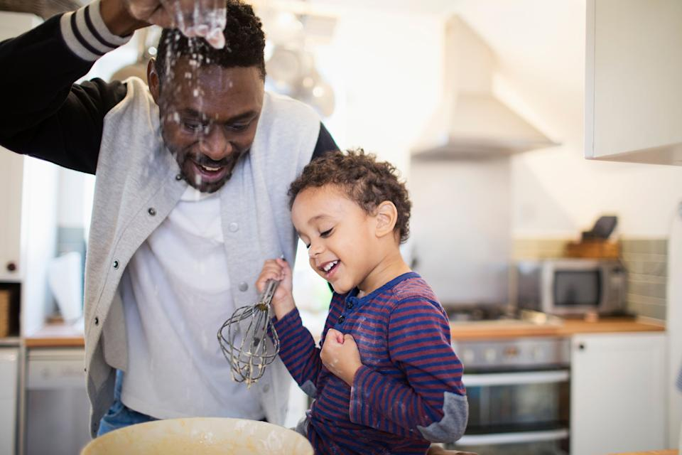 Playful father and son baking in kitchen