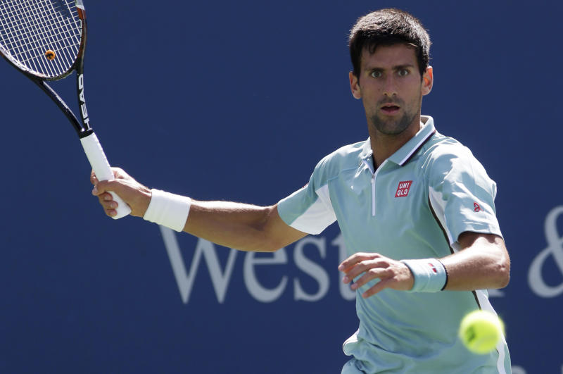 Novak Djokovic, from Serbia, eyes a forehand against Juan Monaco, from Argentina, at the Western & Southern Open tennis tournament, Wednesday, Aug. 14, 2013, in Mason, Ohio. (AP Photo/Al Behrman)