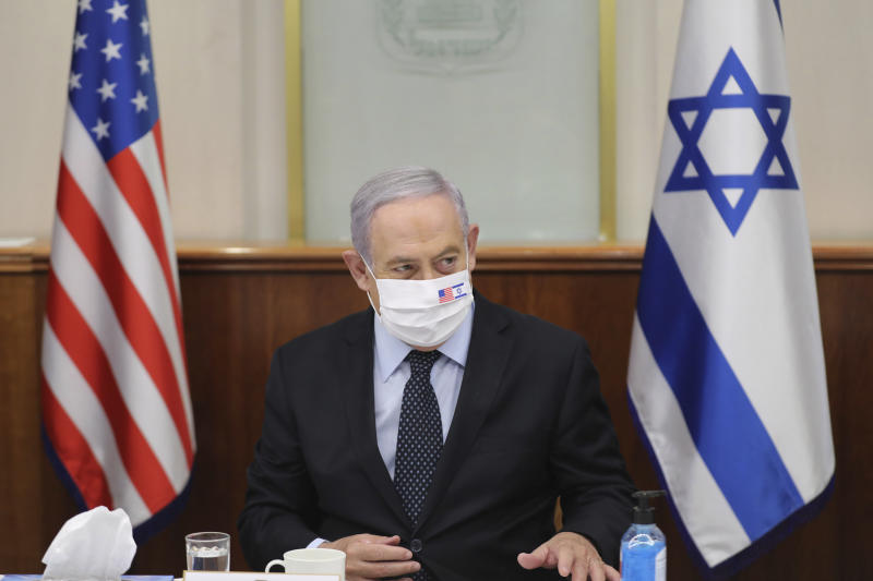 Israeli Prime Minister Benjamin Netanyahu attends a press briefing with US special envoy for Iran, Brian Hook, while wearing a face mask to help prevent the spread of the coronavirus, at the Prime Minister's office in Jerusalem, Tuesday June 30, 2020. (Abir Sultan/Pool via AP)